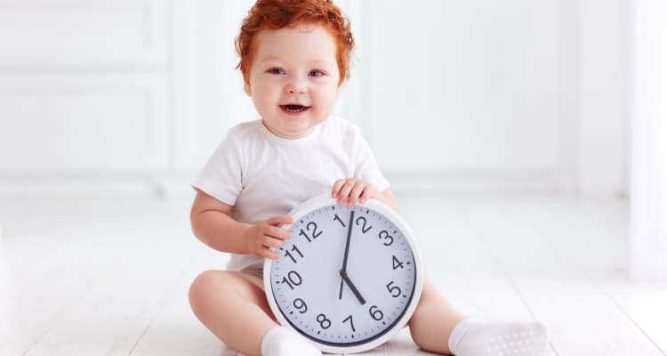 toddler holding a clock
