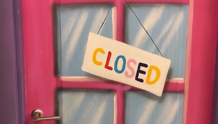 a closed sign hanging over a business