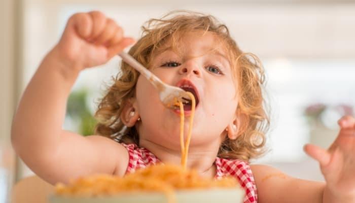 a kid eating spaghetti
