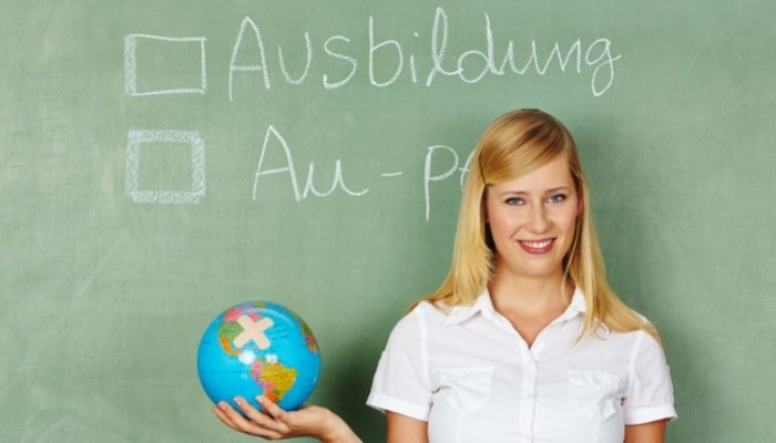 lady standing in front of chalkboard with wording au pair