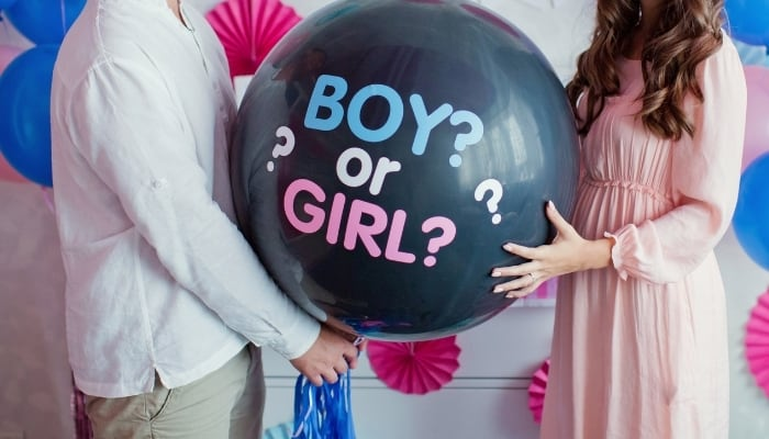 couple holding balloon at gender reveal party