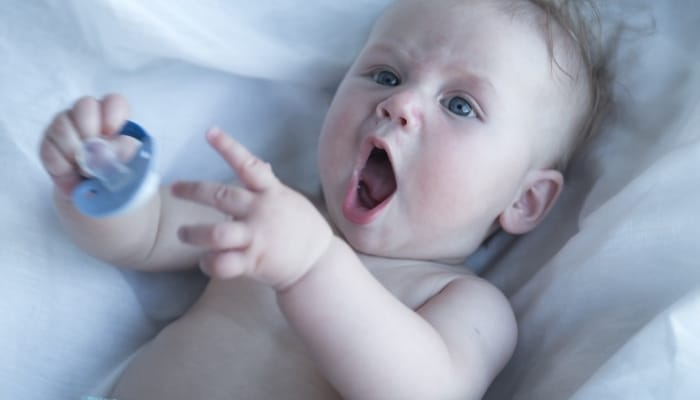 child taking off pacifier
