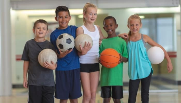 kids holding different types of sports balls