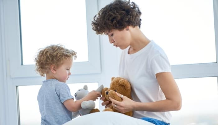 mom playing with teddy bear with child